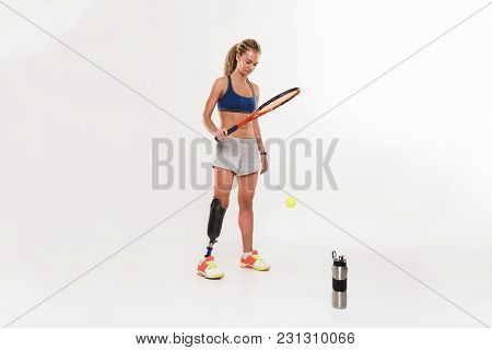 Portrait of a concentrated young disabled sportswoman with leg prosthesis doing exercises with tennis racket isolated over white background