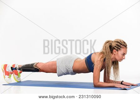 Full length portrait of a confident young disabled sportswoman doing plank exercise on a sports man isolated over white background