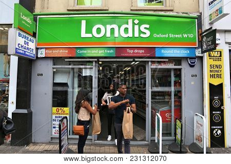 London, Uk - July 7, 2016: Customers Exit Londis Convenience Store In London. Londis Brand Has More