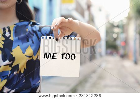 Closeup Of A Young Woman Outdoors Showing A Notepad With The Text Me Too Written In It.