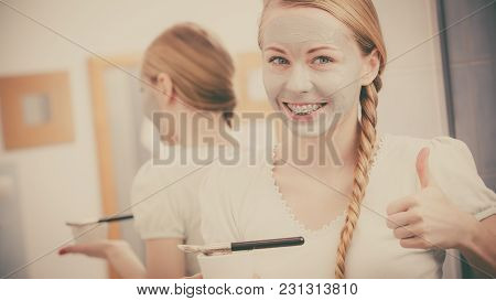 Skincare. Blonde Woman In Bathroom Applying With Brush Gray Clay Mud Mask To Her Face., Making Thumb