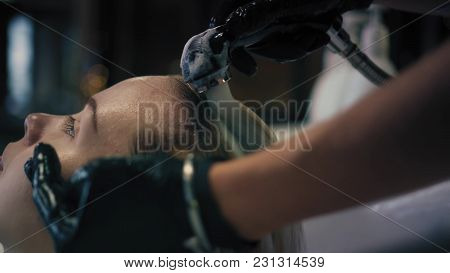 Hairdresser In Black Gloves Carefully Washes Female's Hair With Conditioner In Sink In Hair Salon, A