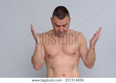 Portrait Of Naked Mature Man Looking Frustrated