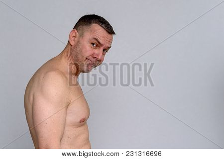 Portrait Of Naked Mature Man Looking Unimpressed