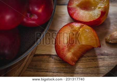 Red Plums On A Wooden Backdrop Showing The Pit And A Bite Out Of One Half.