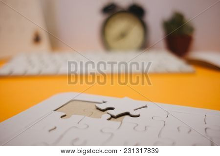 Business Background White Jigsaw Placed On Orange Table With Clock, Keyboard And Copy Space. Image F
