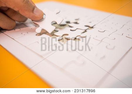 Business Background Hand Of Businessman Pick One Piece Jigsaw Placed On Orange Table With Copy Space