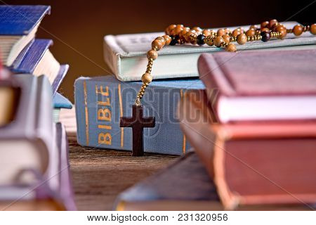 Bible  And Wooden Rosary In The Bookshelf