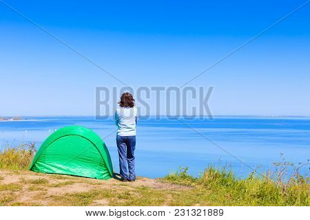 Tourism And Recreation. Small Green Tent In Natural Area Surrounded By Meadow Water Sea Lake. Woman