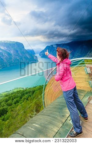Tourist Woman On Stegastein Viewpoint Enjoying Aurland Fjord View Making Thumb Up Gesture Sign, Sogn