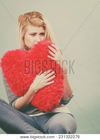 Break Up, Divorce, Bad Relationship Concept. Sad, Depressed Woman Holding Big Red Fluffy Pillow In H