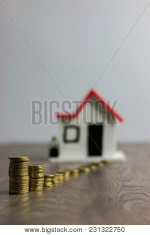 Coins Stacked On Top Of A Wooden Table, With A Blurred House On The Background: Real Estate, Propert