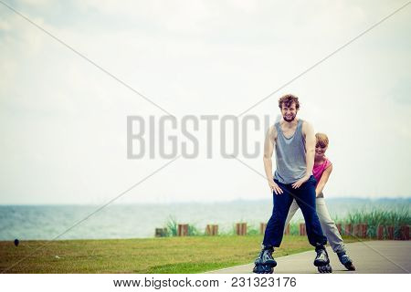Active Lifestyle People And Freedom Concept. Young Fit Couple On Roller Skates Riding Outdoors On Se