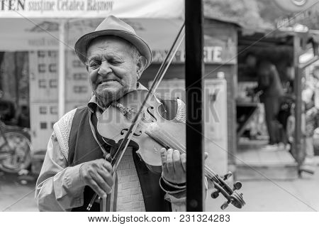 Brasov, Romania-10 August 2017: Old Street Musician  Portrait Near Amusement Park In Black And White