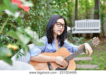 Music Concepts. Asian Girls Playing Guitar. Asian Women Relaxing With Music. Asian Women Have A Happ