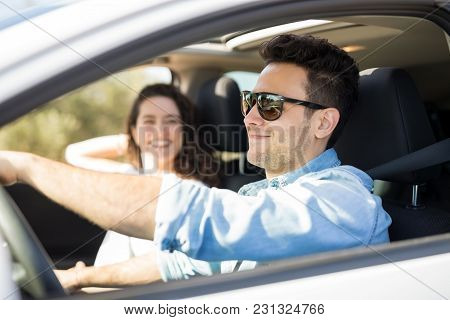 Good Looking Guy On Road Trip With Her Girlfriend. Man Driving A Car With Woman In The Passenger Sea