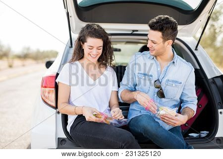 Happy Young Couple Sitting Together In A Trunk Of Their Car And Eating Sandwich During Their Road Tr
