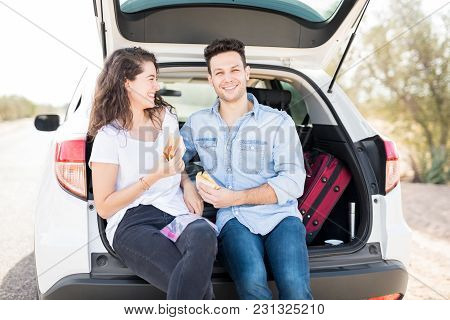 Portrait Of Handsome Young Man With His Girlfriend Sitting In Car Trunk Having Eating Sandwiches