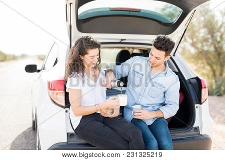 Handsome Young Man Pouring Coffee In The Cup Of His Girlfriend On Road Trip, Couple Sitting In Car T