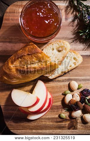 Wooden Platter With Bread, Jam, Apple And Nuts