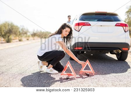 Beautiful Young Woman Putting Red Emergency Stop Triangle Signs On The Road With Broken Car