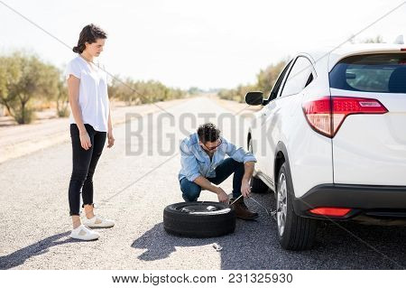 Young Guy Lifting The Car On The Jack For Changing Wheel On A Roadside With Girlfriend Watching