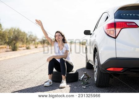 Woman With Flat Tyre On Her Car Hailing Oncoming Traffic On Country Road For Help
