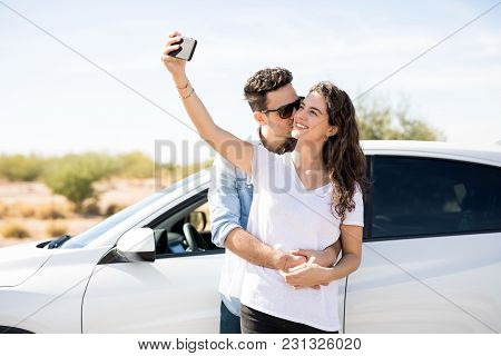 Beautiful Young Woman Taking Selfie With Boyfriend Kissing On Her Cheek While Standing Outdoors By A