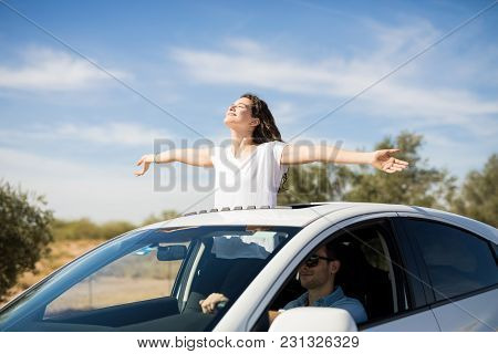 Beautiful Young Couple Is Travelling By Car With Girl Standing Out Of The Sunroof With Arms Outstret
