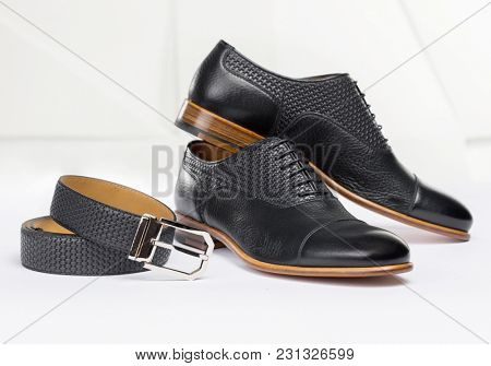 Men's leather shoes and belt on a white background