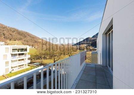 View from balcony of Swiss valley with mountains and trees at the beginning of spring