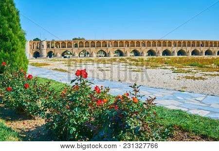 The Historic Preserved Si-o-se-pol Bridge Behind The Red Rose Bushes Of Koudak Park, Isfahan, Iran.
