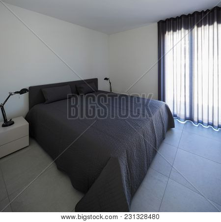 Large bedroom in a modern apartment with a private balcony. Nobody inside