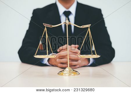 Justice And Law Concept.male Lawyer In The Office With Brass Scale.