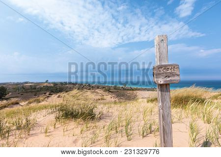 Trail sign designates a hiking path at Sleeping Bear Dunes National Lakeshore, near Glen Arbor Michigan. Lake Michigan can be seen in the background poster