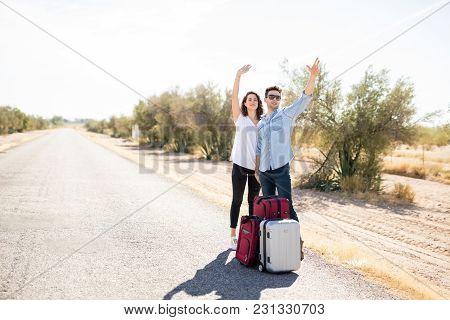 Portrait Of Couple Of Tourist With Luggage Hitchhiking Along On Countryside Road