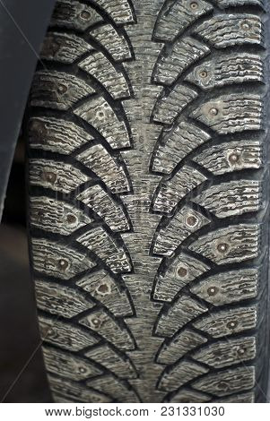 Worn Dirty Tread Of Winter Studded Car Tire