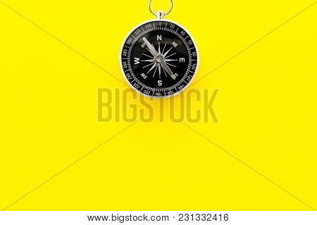 Compass On Yellow Desk Background Top View Copy Space.