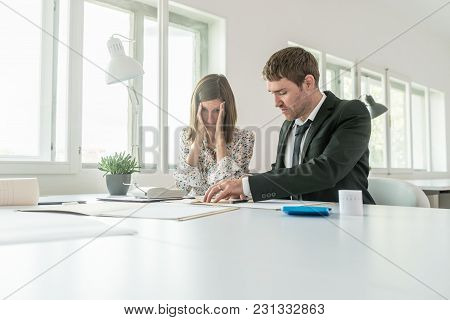 Harassed Businesswoman Checking The Accounts With Her Male Business Partner As They Sit At A Table I