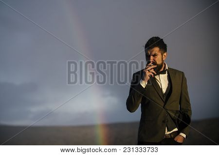 Guy With Strict Face In Suit Feels Free And Successful. Hipster With Stylish Appearance Smoking In F