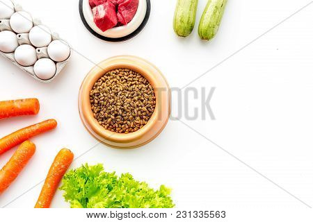 Dry Pet Food With Natural Ingredients. Raw Meat, Vegetables Zucchini And Carrot Near Eggs On White B