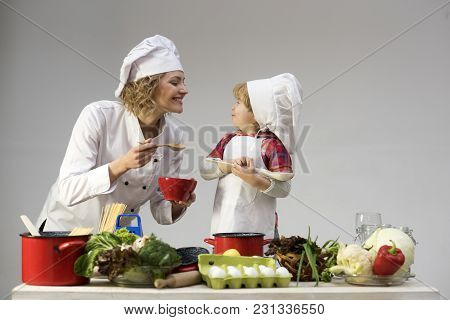 Chef And Assistant Near Kitchen Equipment And Food Products. Mother Teaches Son To Cook On Light Bac