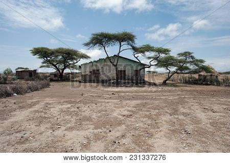 Poor Ethiopian Village Of Several Small Houses Under The Sprawling Trees In The Red Desert Land.