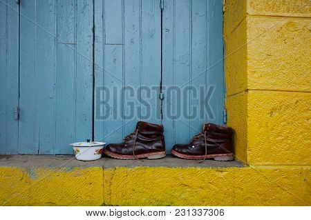 Pair Of Brown Leather Boots Stand On The Slope Of A Yellow Wall Against A Background Of Blue Wooden