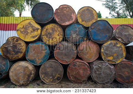 Old Crumpled Iron Barrels With Peeling Paint Are Stacked In A Pile At A Gas Station.