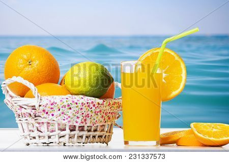 Fresh Orange Juice, Orange Slices And Oranges In Basket Against Background Of Surface Blue Sea. Summ