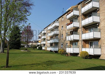 Apartment Bulding With Balconys And A Beautiful Park In The Front