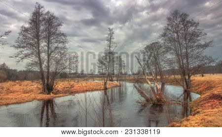 Sad Dark Landscape Of Wild Nature On Rural River With Trees On Shore. Early Spring Nature. Gray Clou