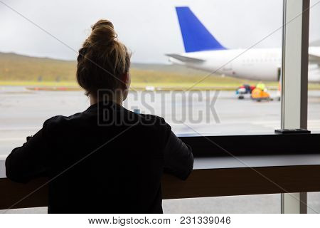 Rear View Of Mid Adult Woman Looking At Airplane Through Window At Airport