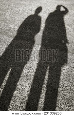 Shadow Of Two People On The Asphalt At Sunset